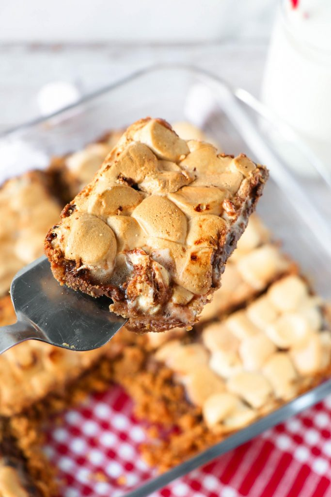 Baking dish of s'mores bars with a piece cut out and held on a serving utensil.