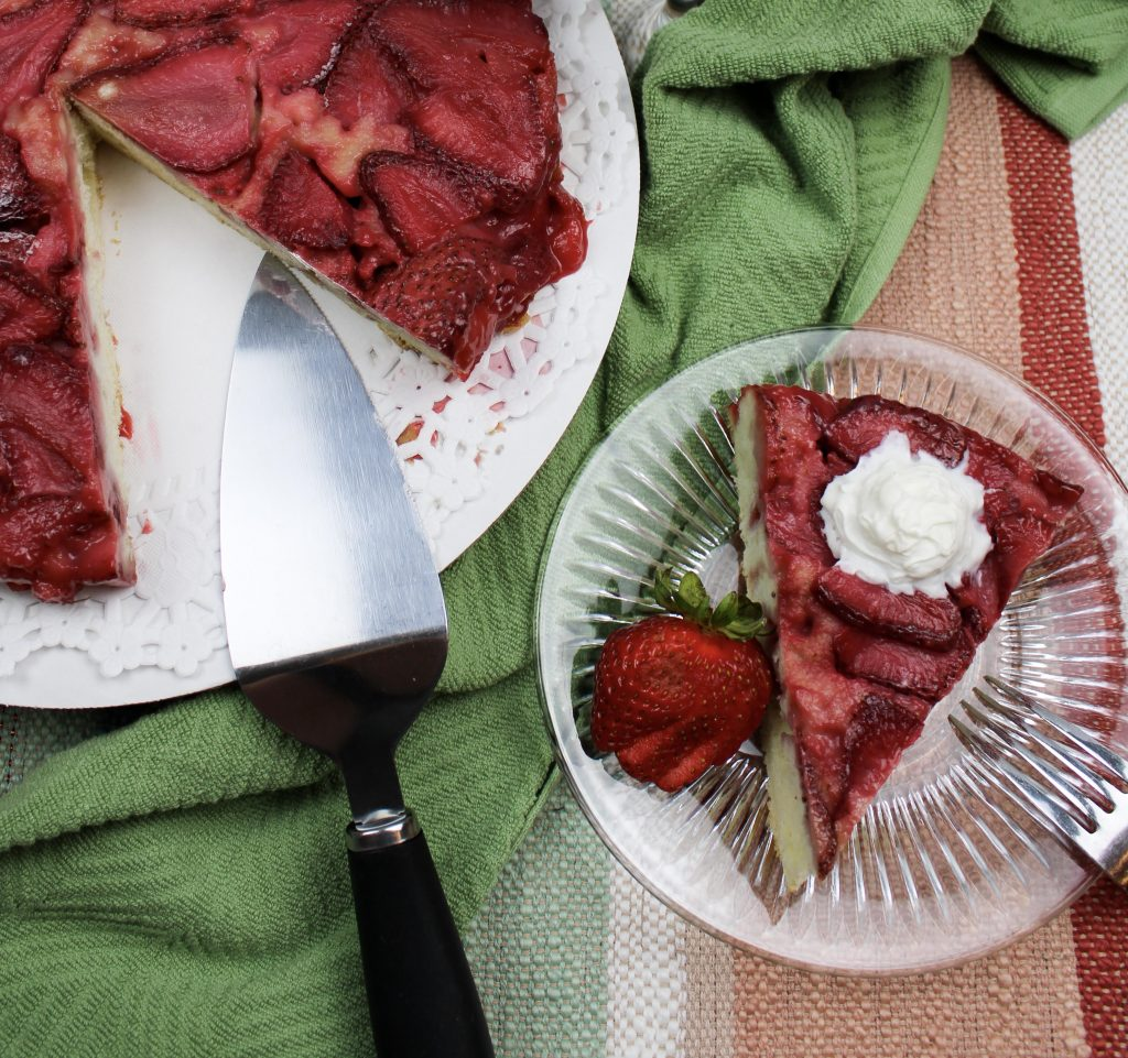 strawberry upside down cake on cake plate with slice cut and put on a dessert plate